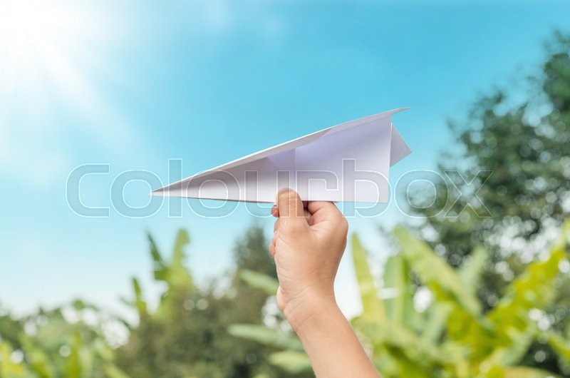 Stock image of 'plane paper in children hand in farm and blue sky, in cloudy day'