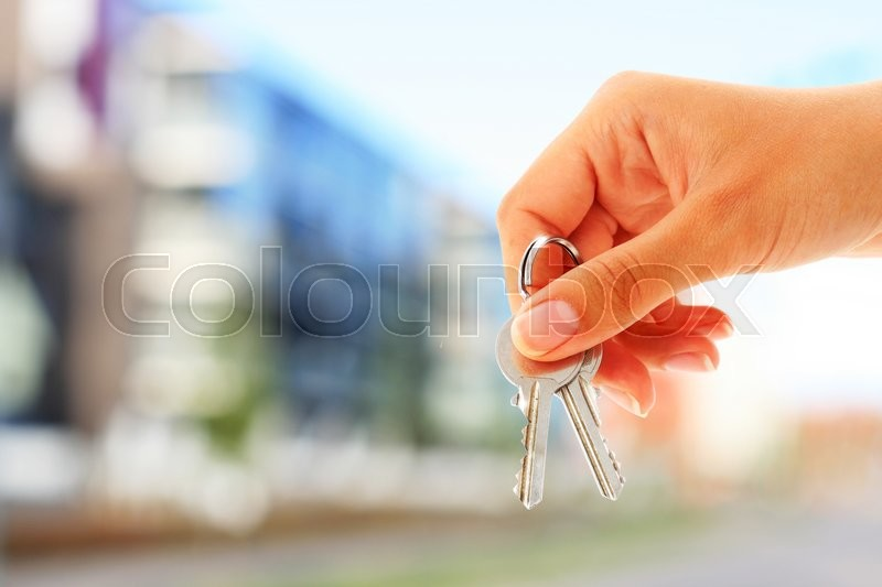 Stock image of 'Key in hand and building on the background'