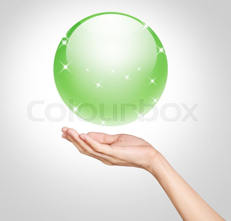Stock image of 'Hands holding up a green translucent ball with star'
