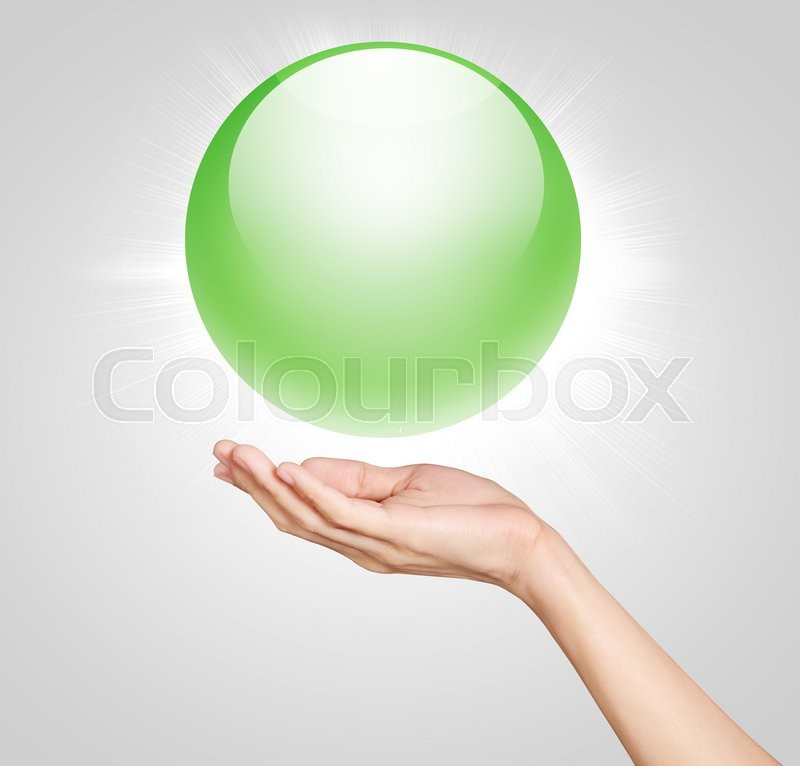 Stock image of 'hands holding up a green translucent ball '