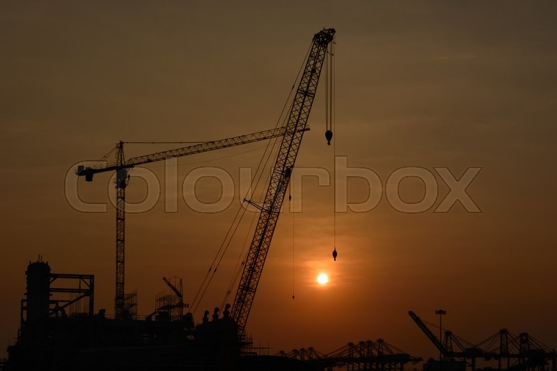 Stock image of 'Crane on a construction site at sunset'