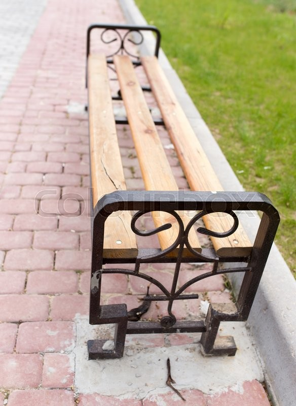 Stock image of 'Bench on the pavement in the park'