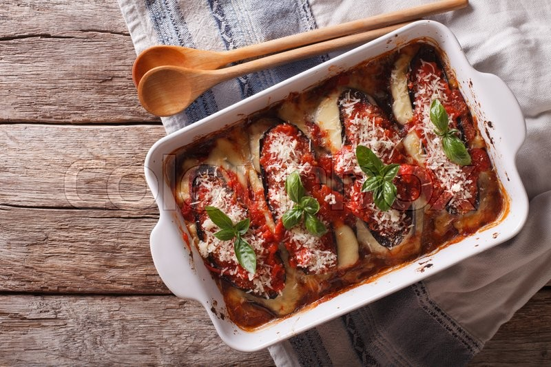 Stock image of 'Italian eggplant baked with mozzarella in tomato sauce close up in baking dish. horizontal view from above\'