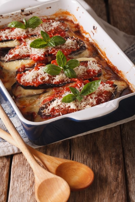 Stock image of 'Italian eggplant Melanzane alla parmigiana close up in baking dish on the table. vertical\'