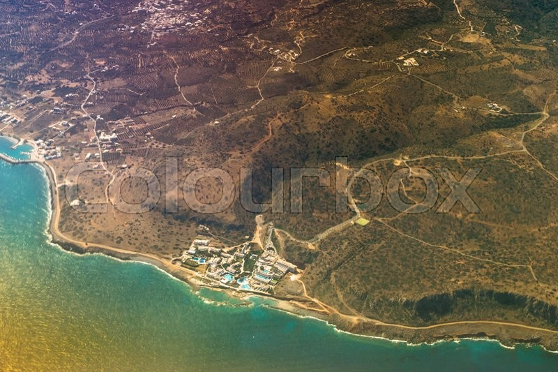 Stock image of 'Seaside view of resort Crete island with hotels and beaches, aerial view from flight altitude of aircraft. Sun reflected from the water surface through the clouds. Mountainous landscape and roads-serpentines. Greece'