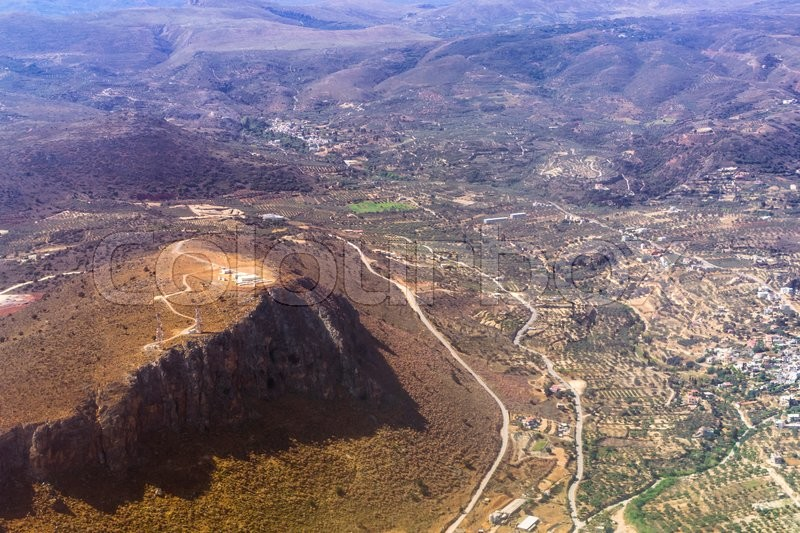 Stock image of 'Aerial view of resort Crete island, flight altitude of aircraft. Mountainous landscape and roads-serpentines. Greece'