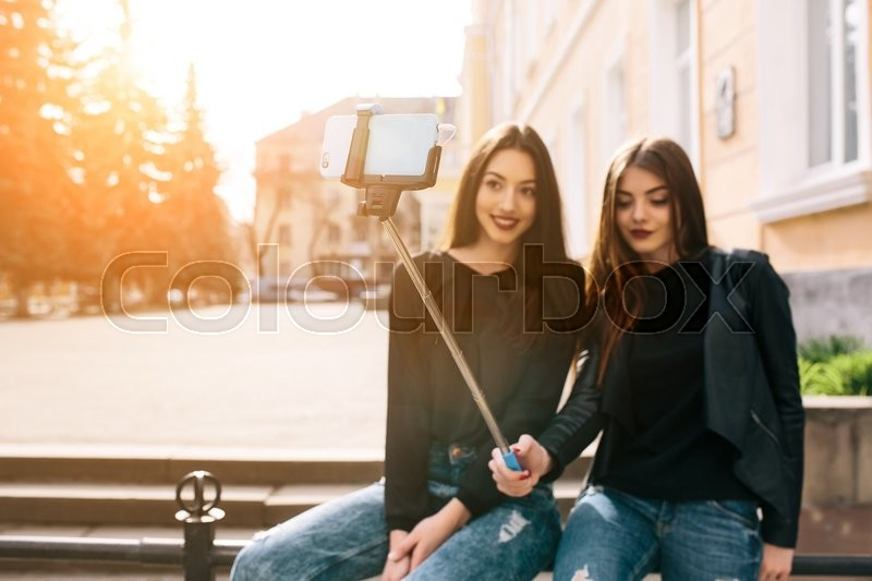Stock image of 'Two young adult women sitting on the bench and make selfie'