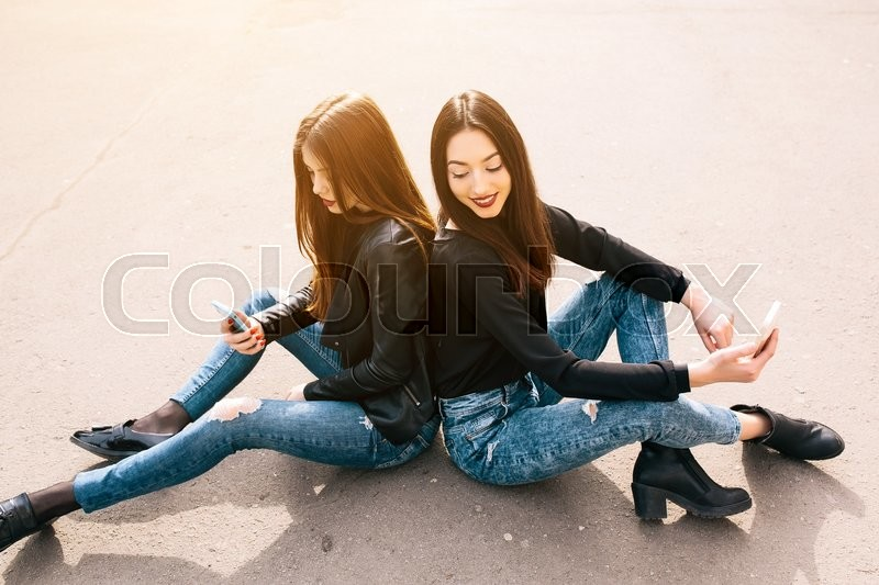 Stock image of 'Two young adult women sitting outside and watching something in the smartphone'