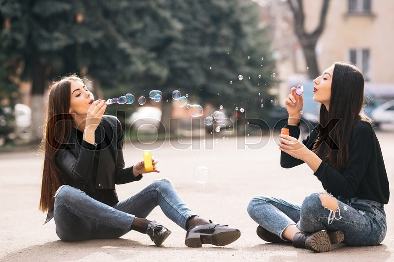 Stock image of 'Two young adult girls sitting in a park and blow bubbles'