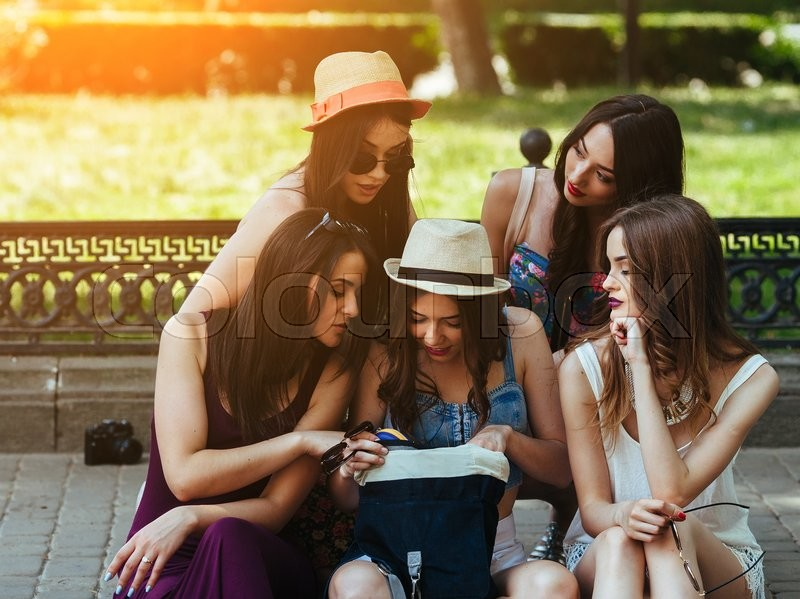 Stock image of 'five beautiful young girls consider the bag in the park'