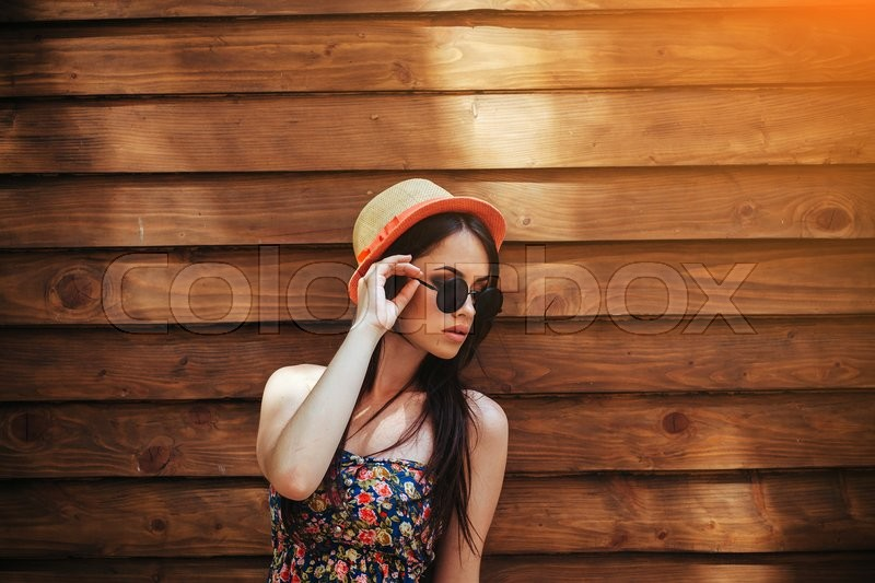 Stock image of 'beautiful girl in sunglasses posing for the camera on brown background'