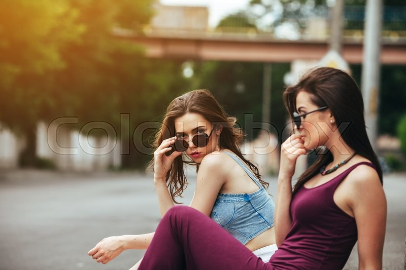 Stock image of 'Two beautiful young girls posing on the background of the urban landscape'