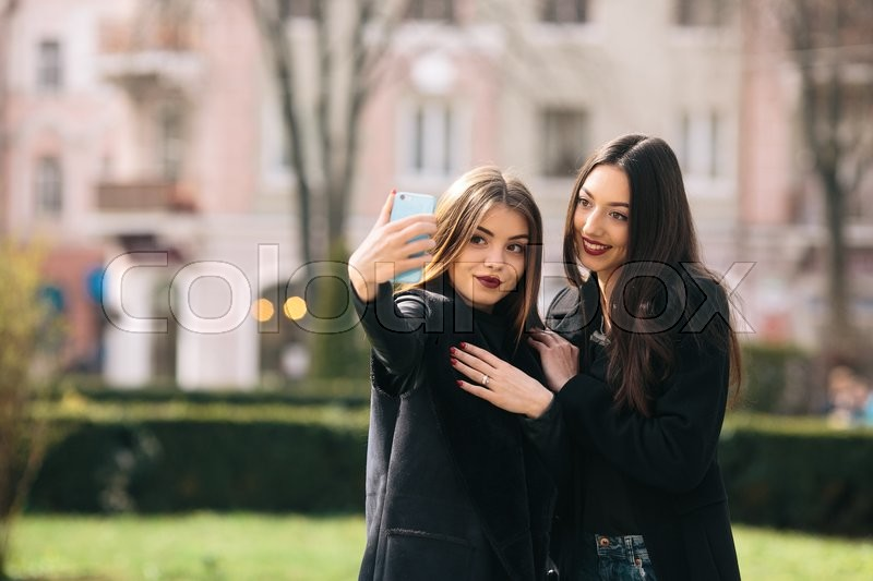 Stock image of 'Two young adult girls make selfie on a city street'