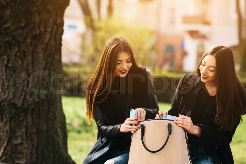 Stock image of 'Two young adult women sitting in the street and looking for something in a bag'