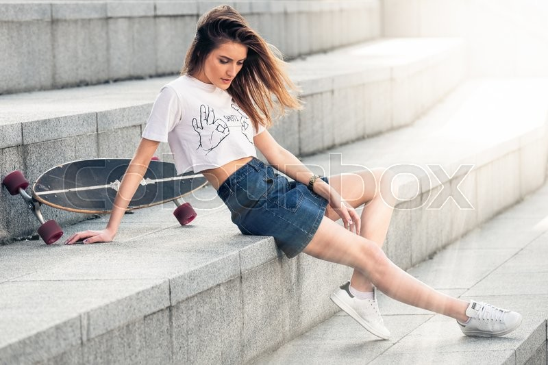 Stock image of 'Outdoor closeup portrait of pretty stylish fashion girl having fun girl sits on concrete stairs with a longboard outdoors. Young woman city portrait in summer street sunny day, horizontal picture.'