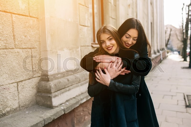 Stock image of 'Two young adult women posing on a city street'