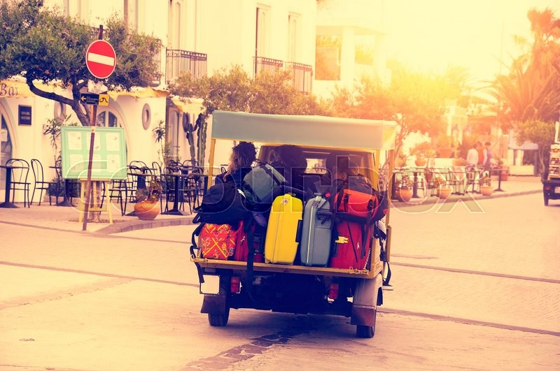 Stock image of 'Tourists with the luggage moves to the hotel by mototaxi on the resort at sunset.'