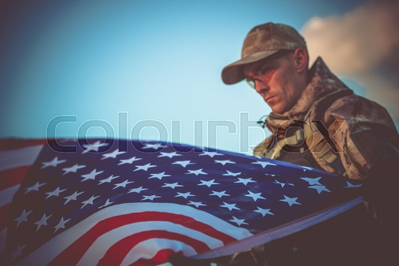 Young Army Veteran with American Flag Closeup Photo. Army Trooper with USA Flag, stock photo