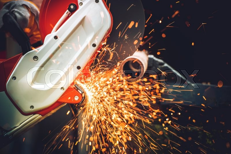 Stock image of 'Heavy Duty Construction Works. Metal Cut Using Compact Electric Metal Cutter.'