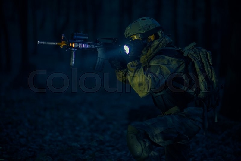 Stock image of 'Military Night Operation. Soldier with Assault Rifle and Flashlights at Night.'