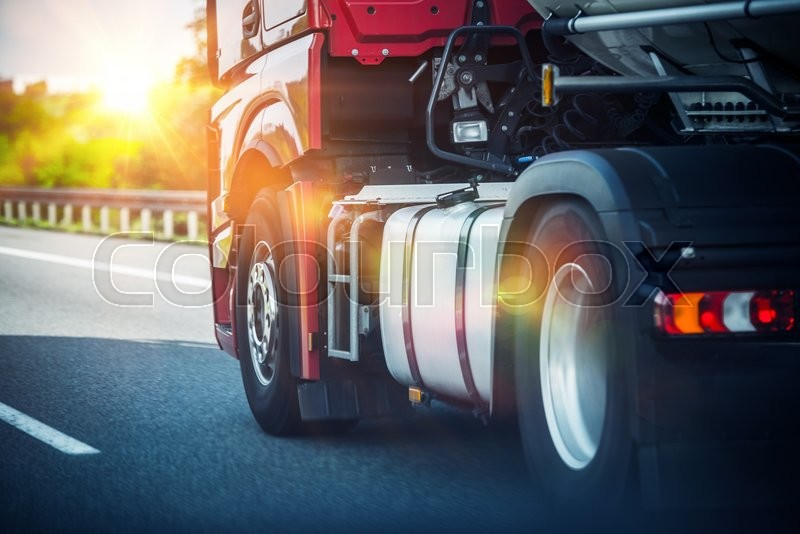 Stock image of 'Red Semi Truck Speeding on a Highway. Tractor Closeup. Transportation and Logistics Theme.'