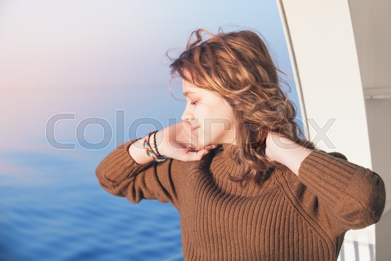 Stock image of 'Beautiful happy blond teenage girl stands on the walking deck of cruise ship, close-up outdoor portrait'