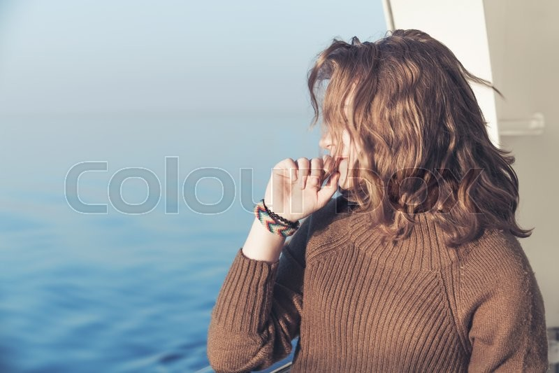 Stock image of 'Beautiful relaxing blond teenage girl stands on the walking deck of cruise ship, close-up outdoor portrait'