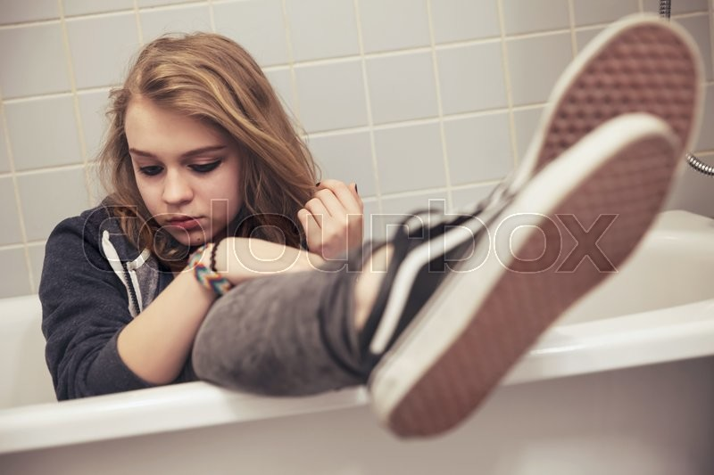 Stock image of 'Teenage girl in black sporty sneakers sits in white bath. Closeup photo with selective focus on face, tonal filter correction, vintage stylized'