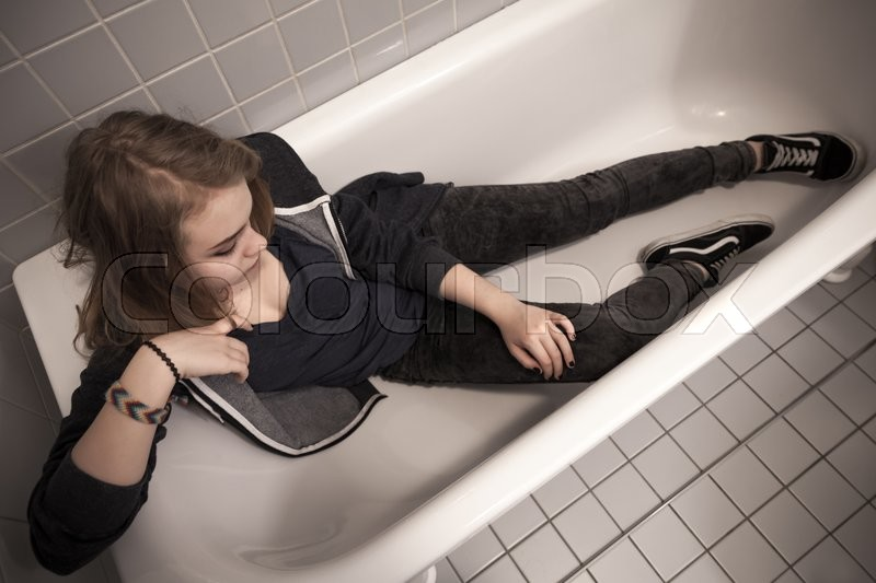 Stock image of 'Caucasian blond teenage girl sitting in empty bath. Stylized photo, tonal filter correction, vintage stylized with old style effect'