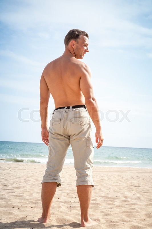 Stock image of 'Barefoot sporty man stands on sandy summer beach'