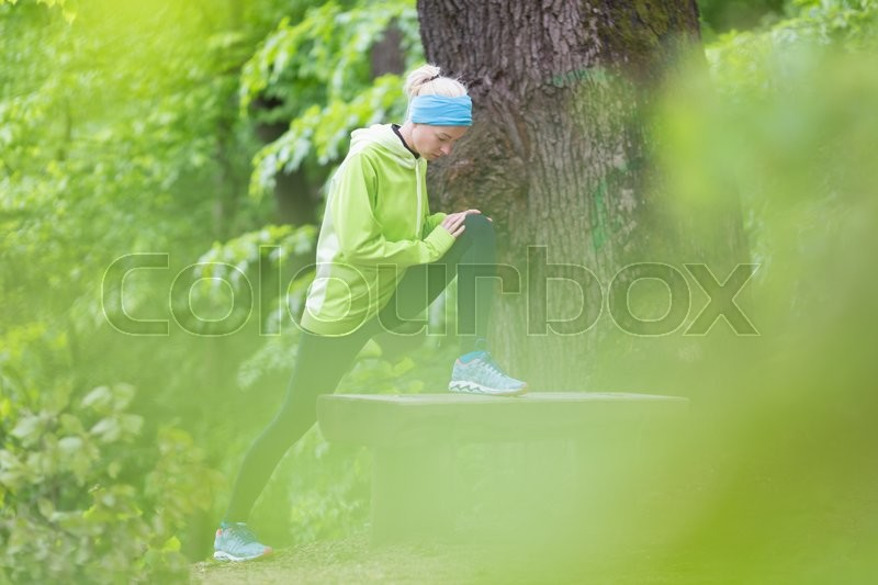 Stock image of 'Sporty young female working out in forest.  Female runner during stretching exercise in nature. Fitness model outdoors. Weight Loss. Healthy lifestyle. '