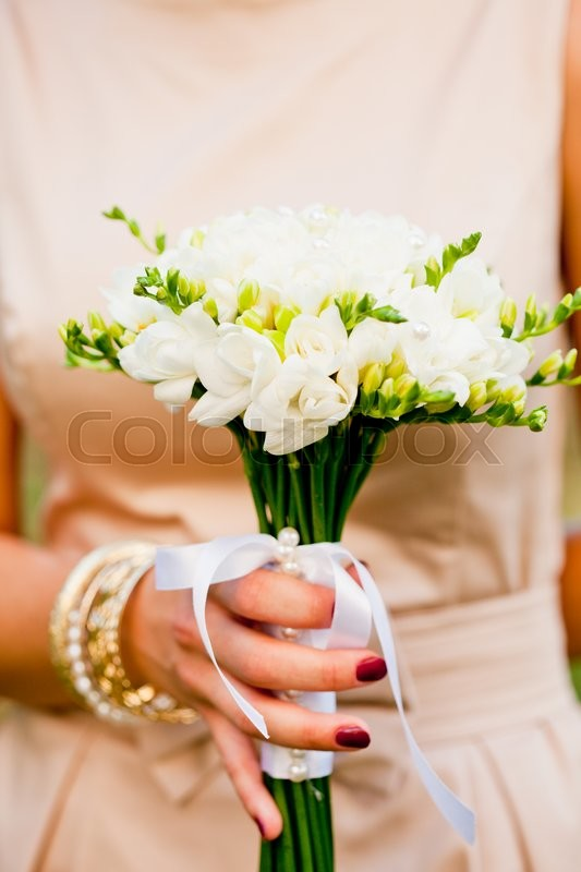 Stock image of 'Wedding bouquet with white freesias closeup in bride's hands'