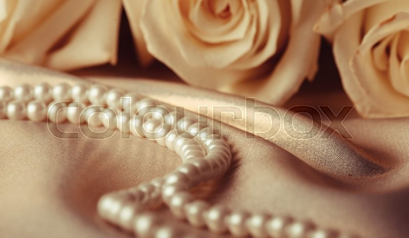 Stock image of 'Pearl beads and cream rose on the silk background'