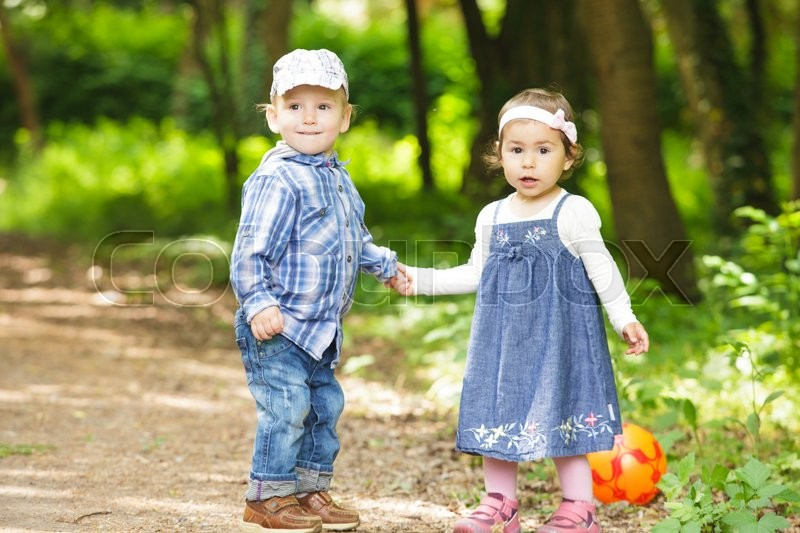 Stock image of 'Boy and girl are playing with ball outdoor'