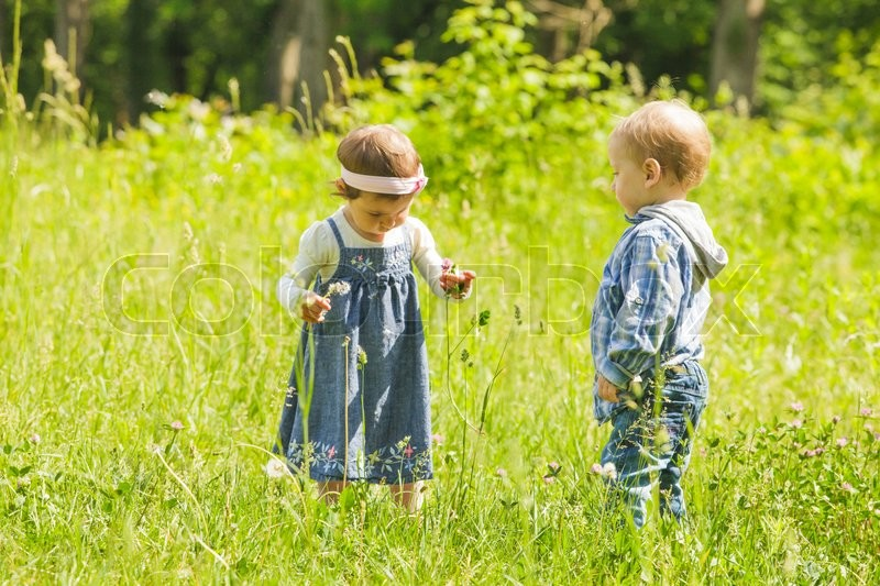 Stock image of 'Boy gives a flower to girl. Little kids play outdoors'