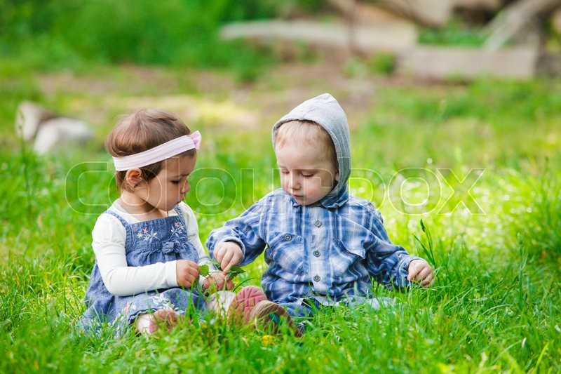 Stock image of 'Little kids play outdoors on the grass'