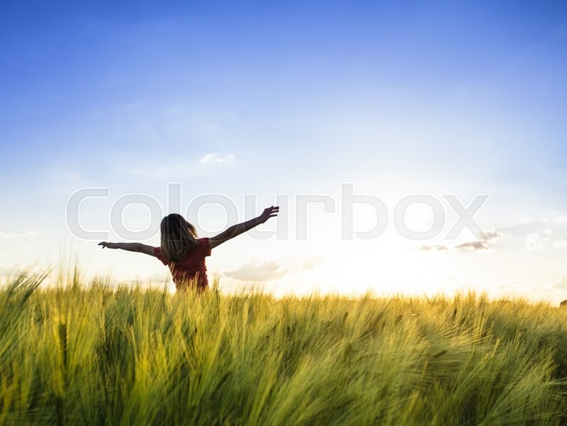 Stock image of 'Teenage girl enjoy with sunshine in wheat field'