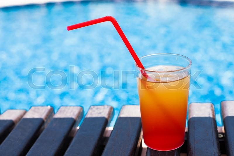 Stock image of 'The orange refreshing cocktail with red straw near swimming pool'