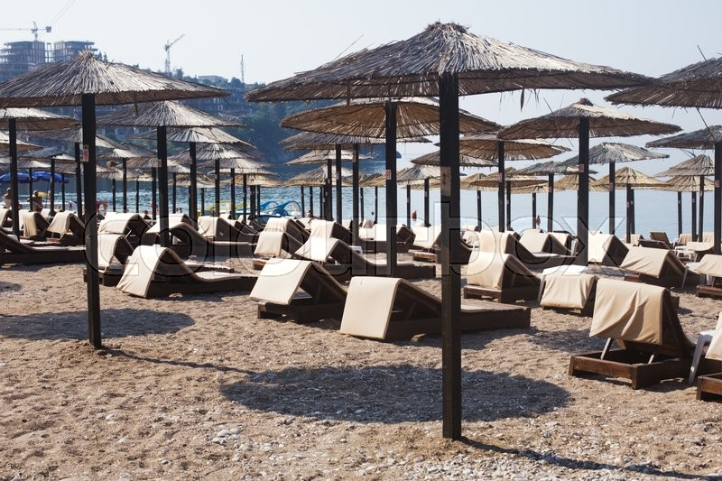Stock image of 'Rows of brown wooden lounge chairs and straw beach umbrellas on sea beach in the morning. Budva, Montenegro'
