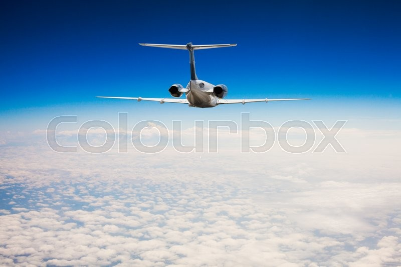 Stock image of 'Rear view of a airplane that is flying high above the clouds'
