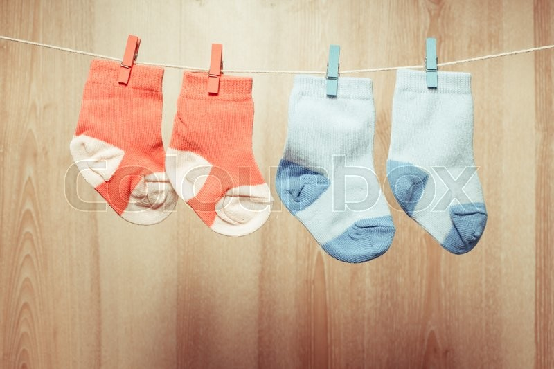 Stock image of 'Baby girl and boy socks attached to the rope'
