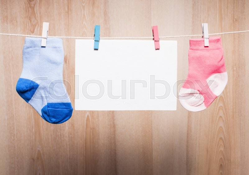 Stock image of 'Baby boy and girl socks attached to the rope and blank card for greetings'
