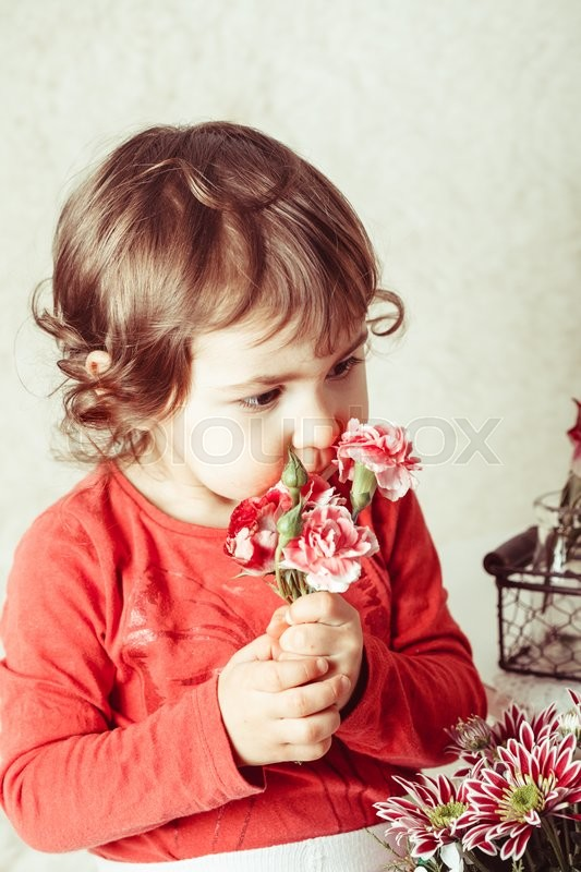Stock image of 'Little girl is smelling the roses. Close up face'