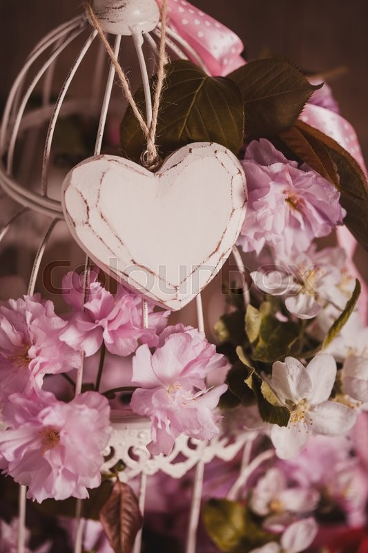 Stock image of 'Bird cage with wooden heart with sakura and apple flowers. Wedding decorations with pink ribbon with copy space'