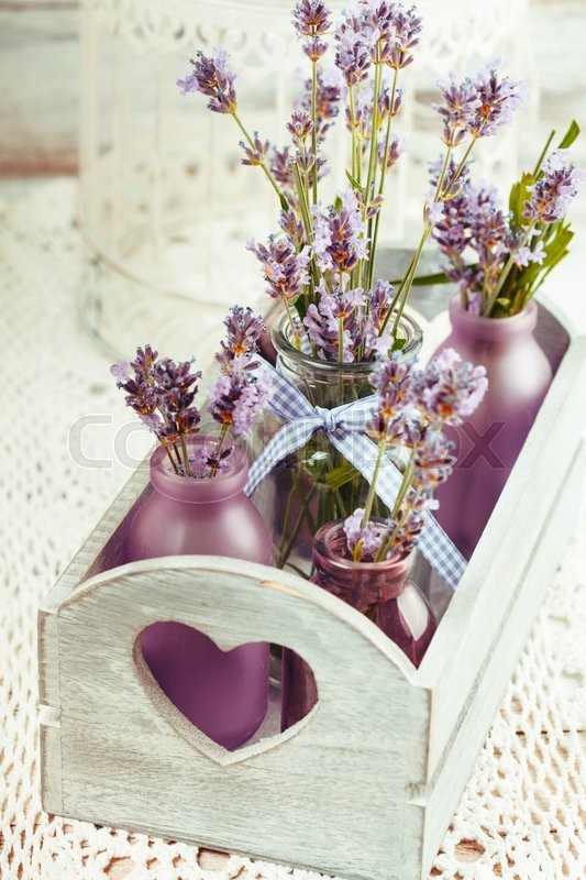 Stock image of 'Lavender in bottles, decor provance style, wooden box and birdcage on crochet tablecloth'