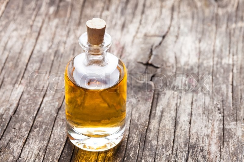 Stock image of 'A large glass bottle of essential oil on a wooden floor'