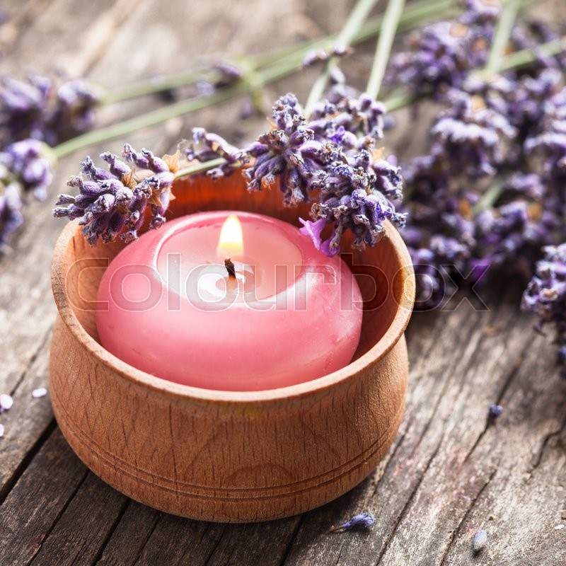 Stock image of 'Sprig of fragrant lavender alongside a burning aromatic candle'