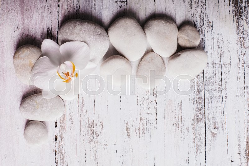 Stock image of 'White orchid on the rebbles, spa concept with copy space'