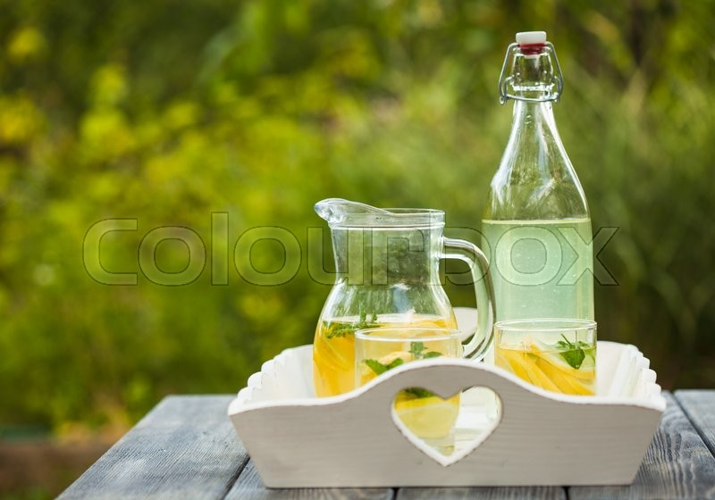 Stock image of 'Lemonade drink in the glasses and jug on the white tray'