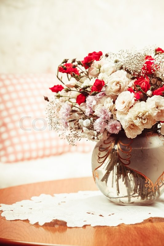 Stock image of 'Flower bouquet on the table near the sofa with a pillow'